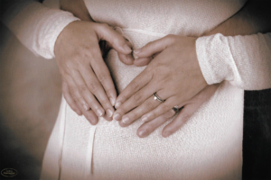 Couple's hands on mother's pregnant belly after mini IVF success | Tennessee Reproductive Medicine | Chattanooga